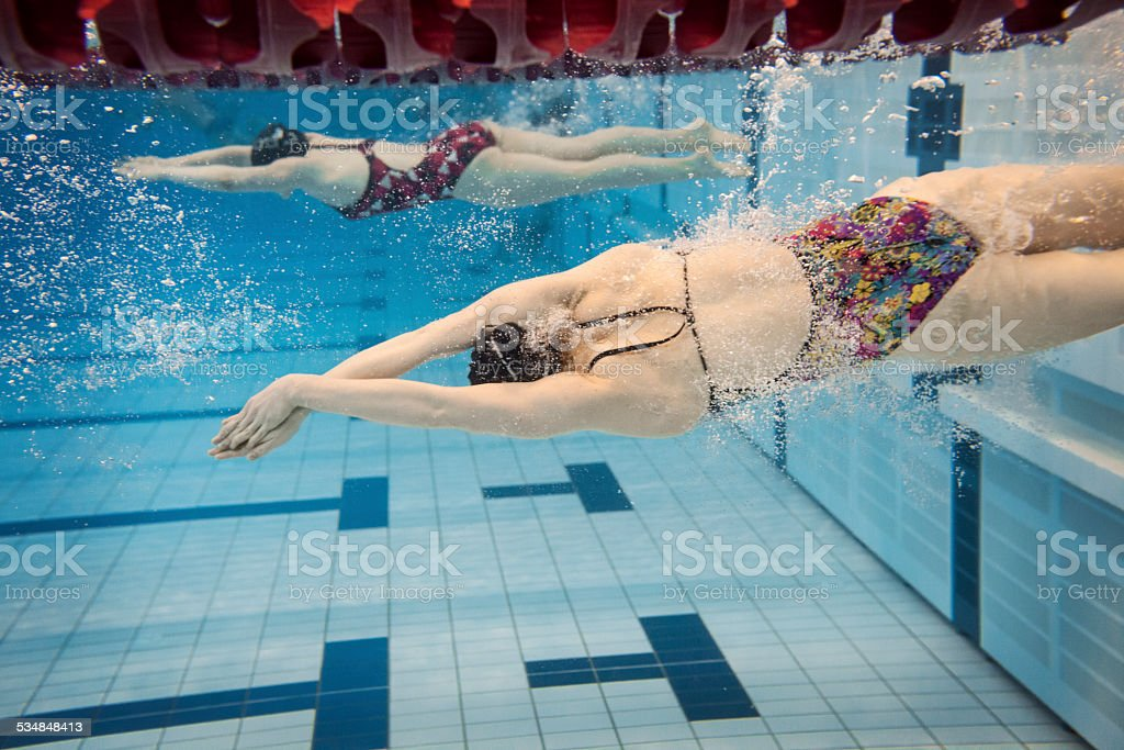 Female Swimmers Performing Flip Turn stock photo