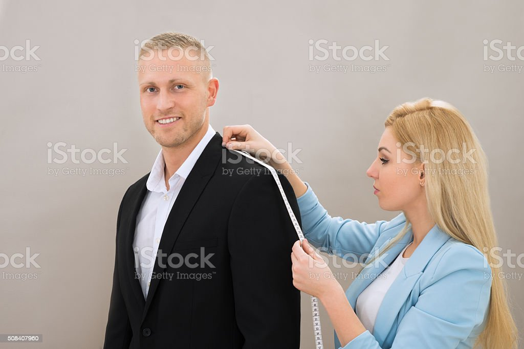 Female Tailor Taking Measurement Of Suit stock photo