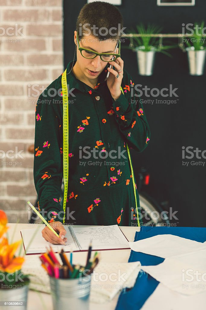 Female Tailor Talking On The Phone In Her Workshop stock photo
