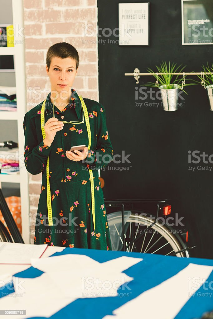 Female Tailor Texting In Her Workshop stock photo