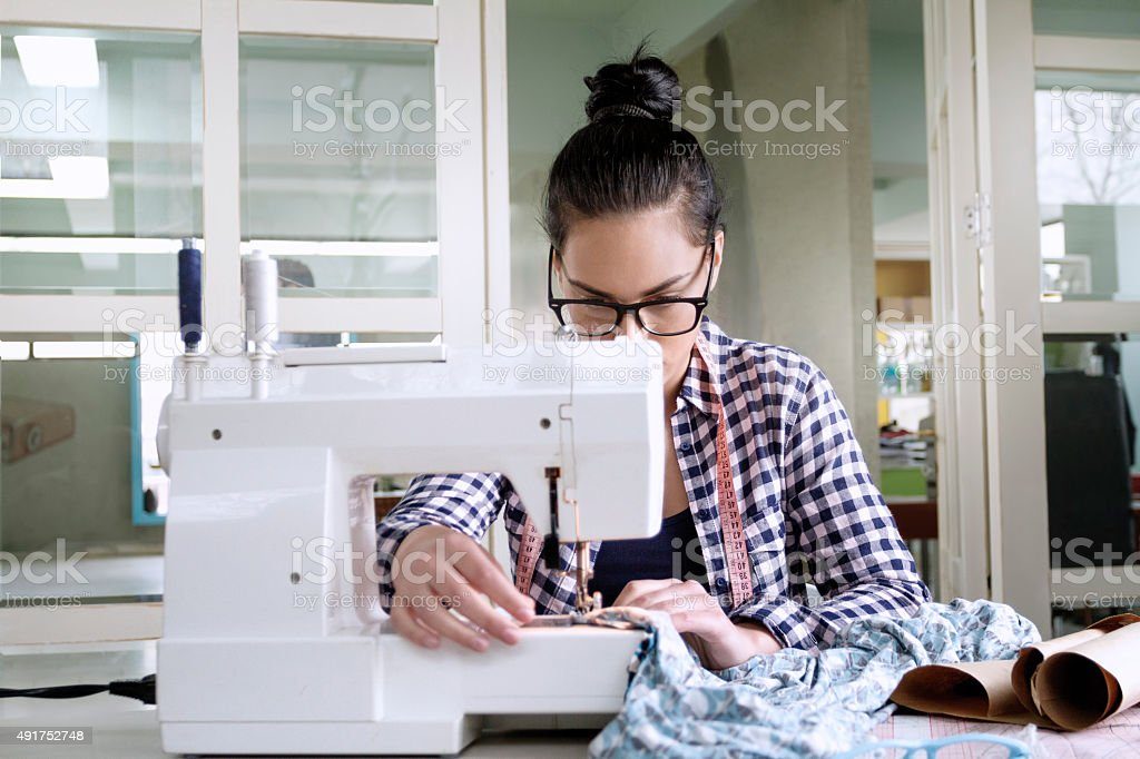 Female tailor working on sewing machine stock photo
