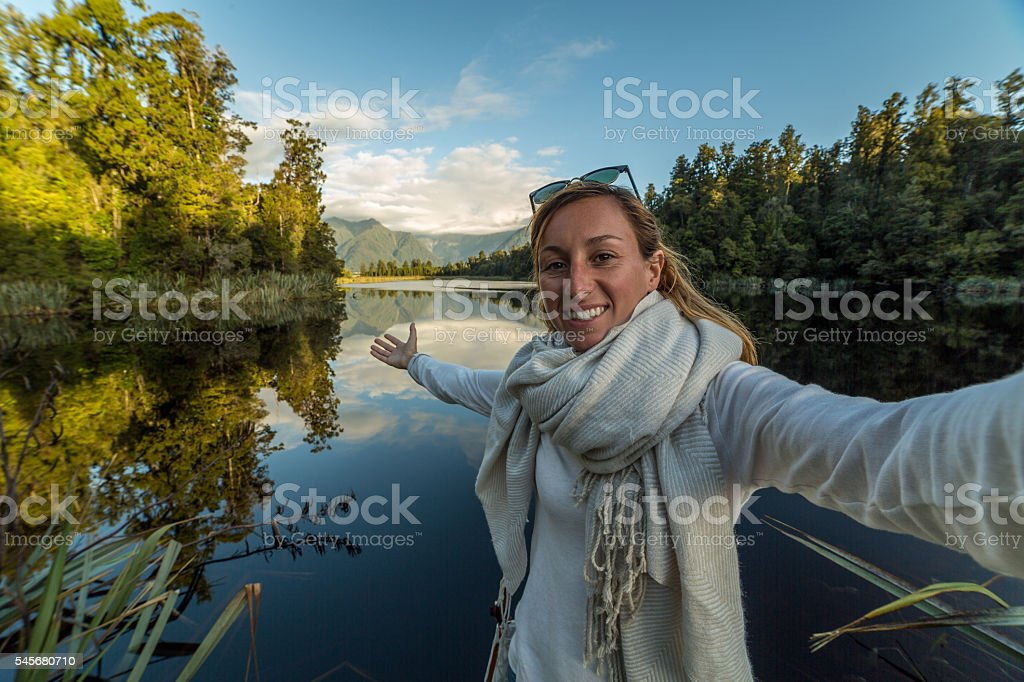 Female takes self portrait at lake Matheson, NZ stock photo