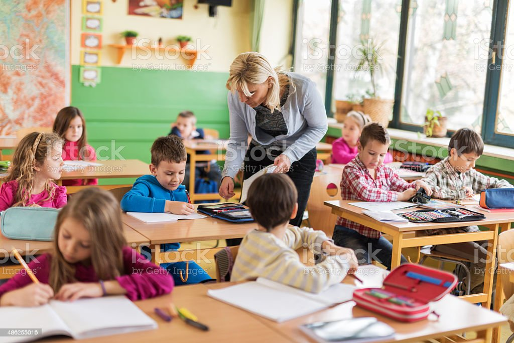 Female teacher assisting elementary students in the classroom. stock photo