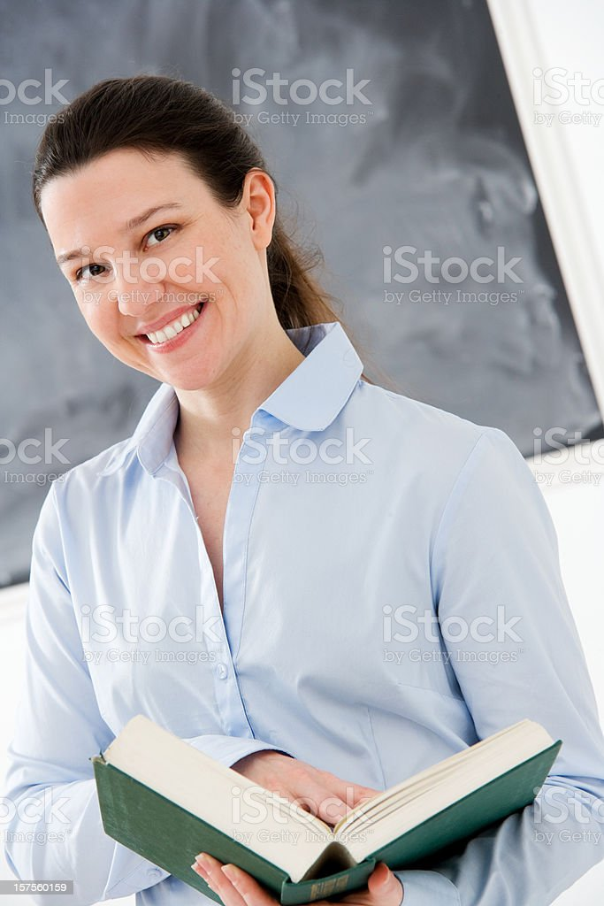 Female Teacher in Classroom Holding Open Book royalty-free stock photo