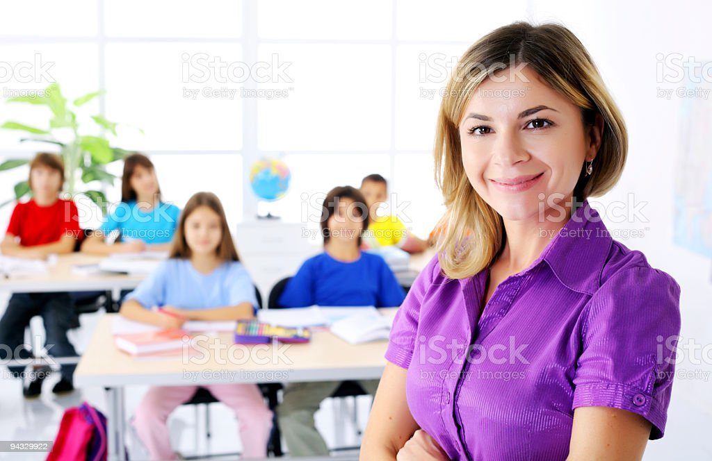 Female teacher standing on the foreground in a class room. stock photo