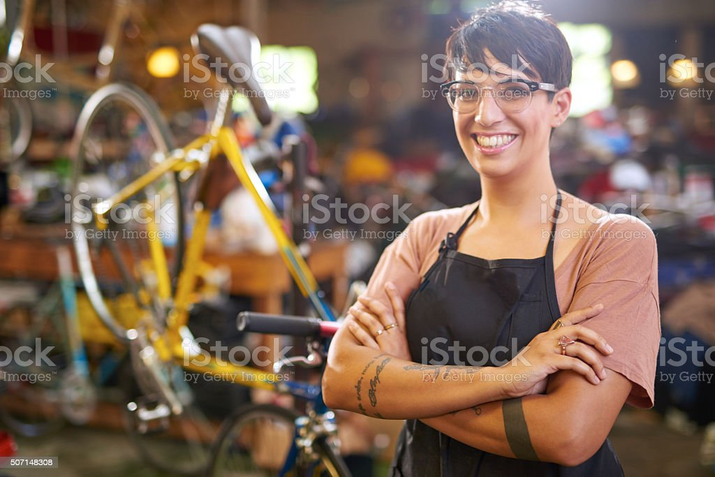 Female technician in her bicycle repair shop stock photo