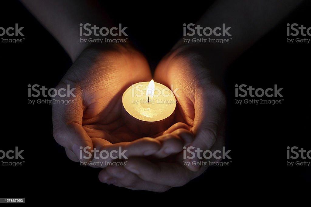 Female teen hands holding burning tea candle stock photo