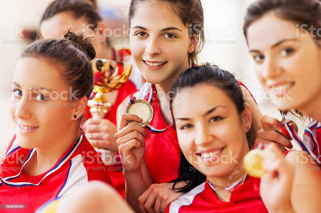 Female teenage volleyball team holding champion cup. royalty-free stock photo