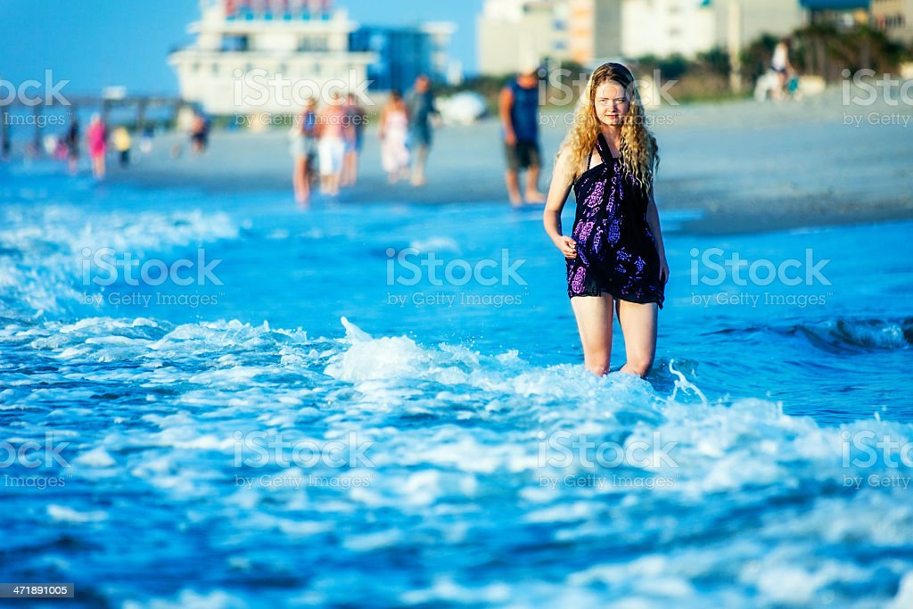 Female Teenager Alone in a Crowd on Beach royalty-free stock photo