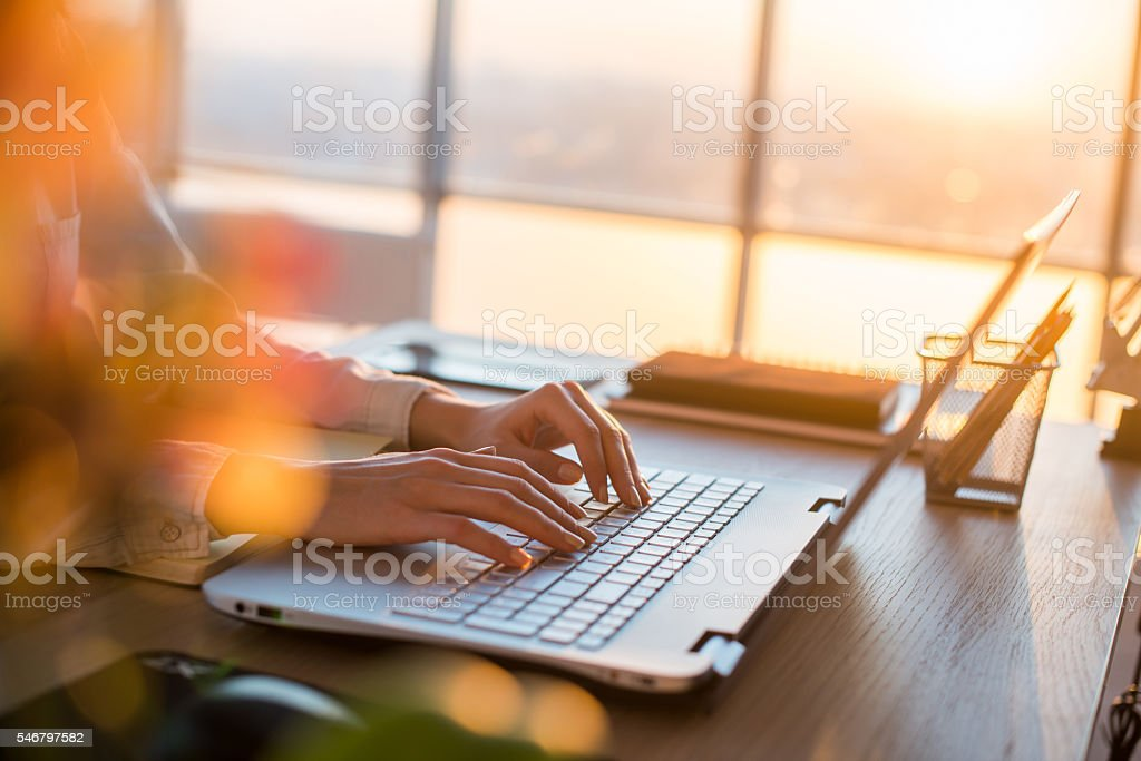 Female teleworker texting using laptop and internet, working online. Freelancer stock photo