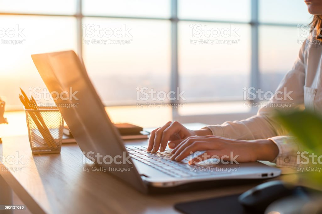 Female teleworker texting using laptop and internet, working online. Freelancer typing at home office, workplace. stock photo