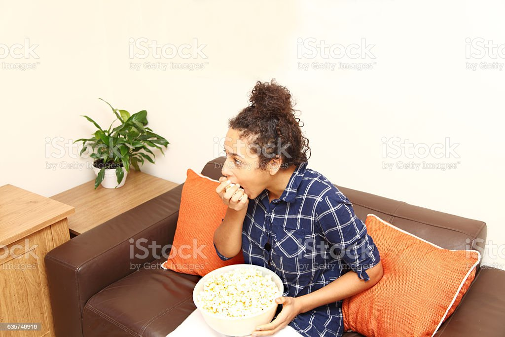 female tenager eating popcorn while watching television. stock photo