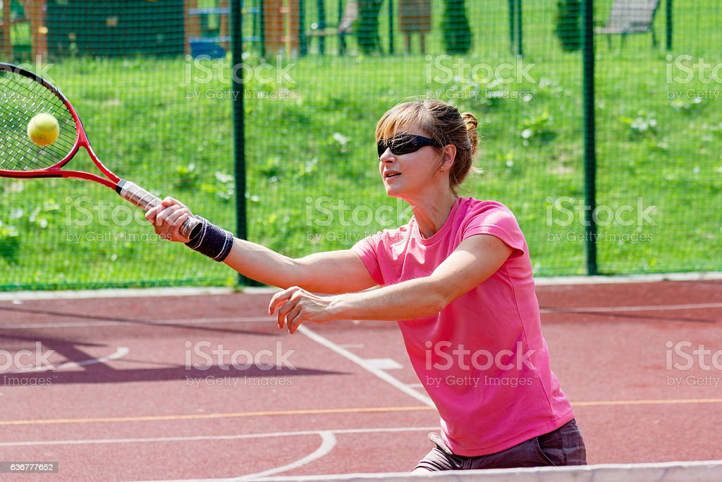 Female tennis player hitting a volley stock photo