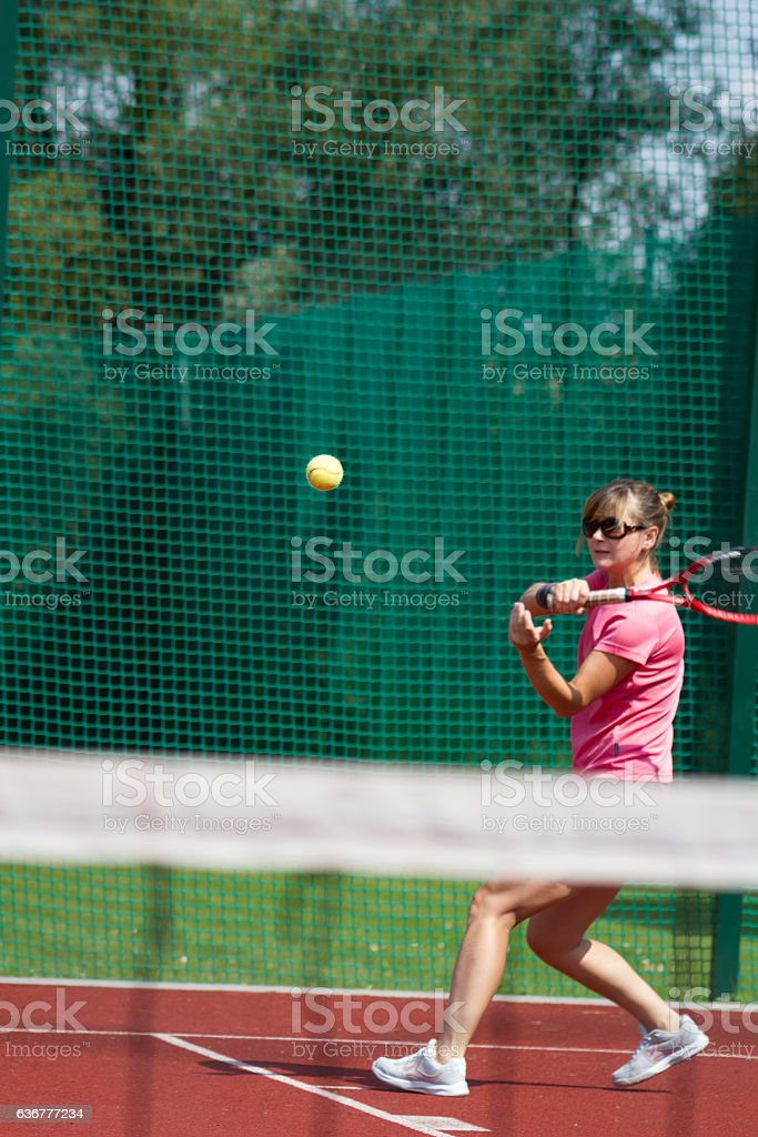 Female tennis player hitting forehand. Focus on ball. stock photo