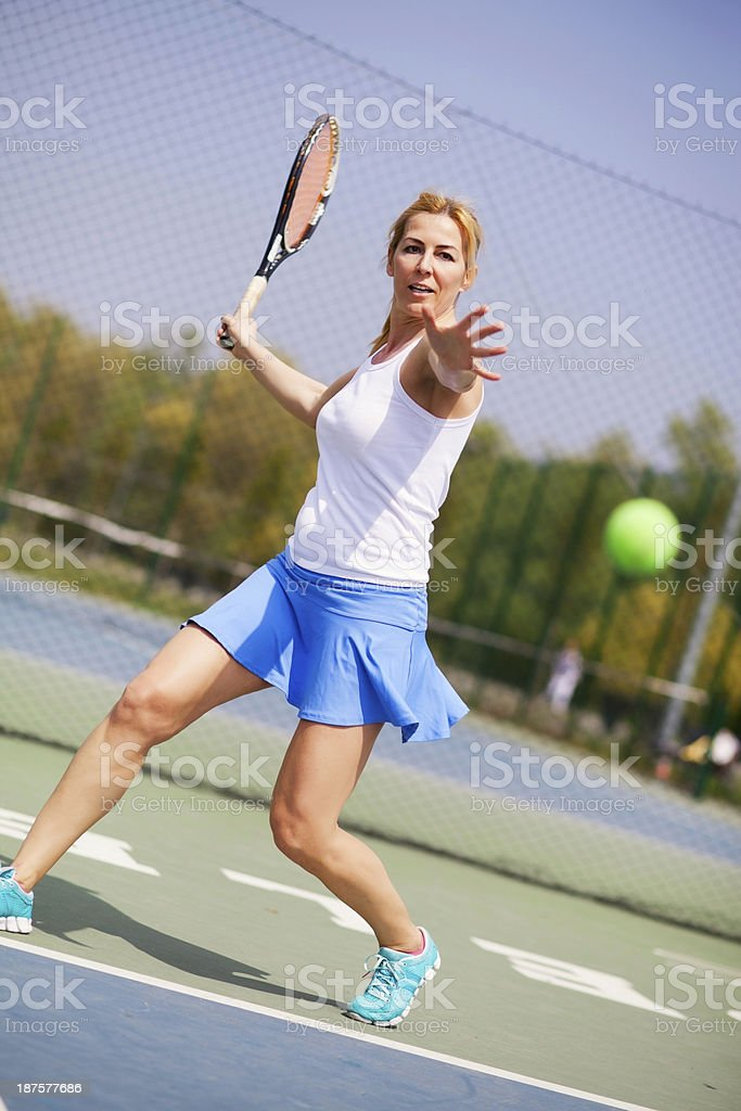 Female tennis player hitting the ball. stock photo