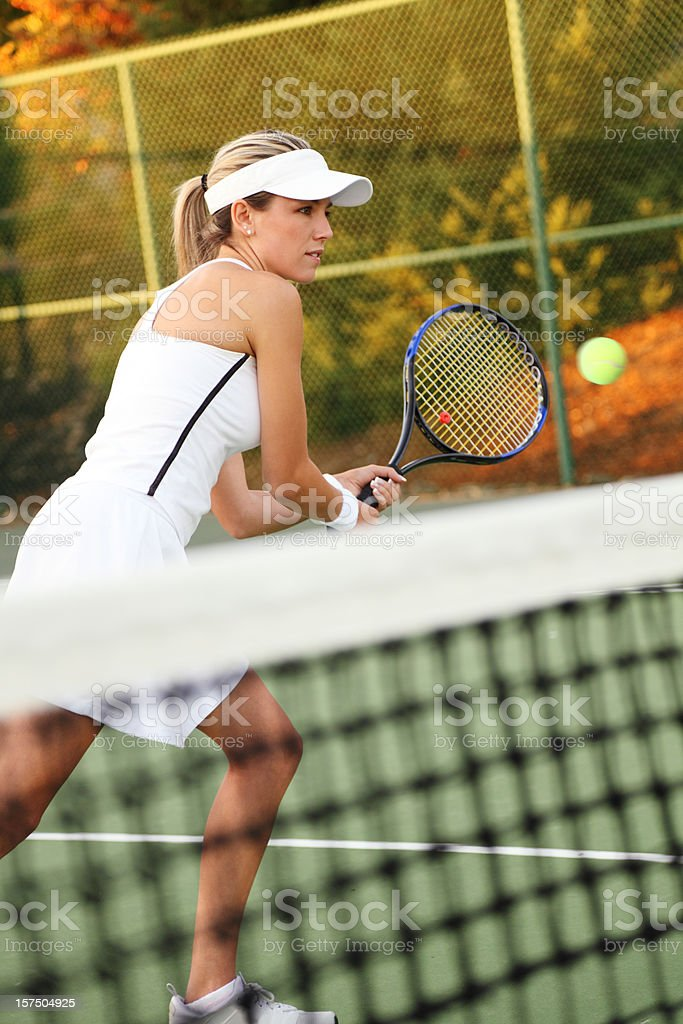 A female tennis player in action on a court royalty-free stock photo