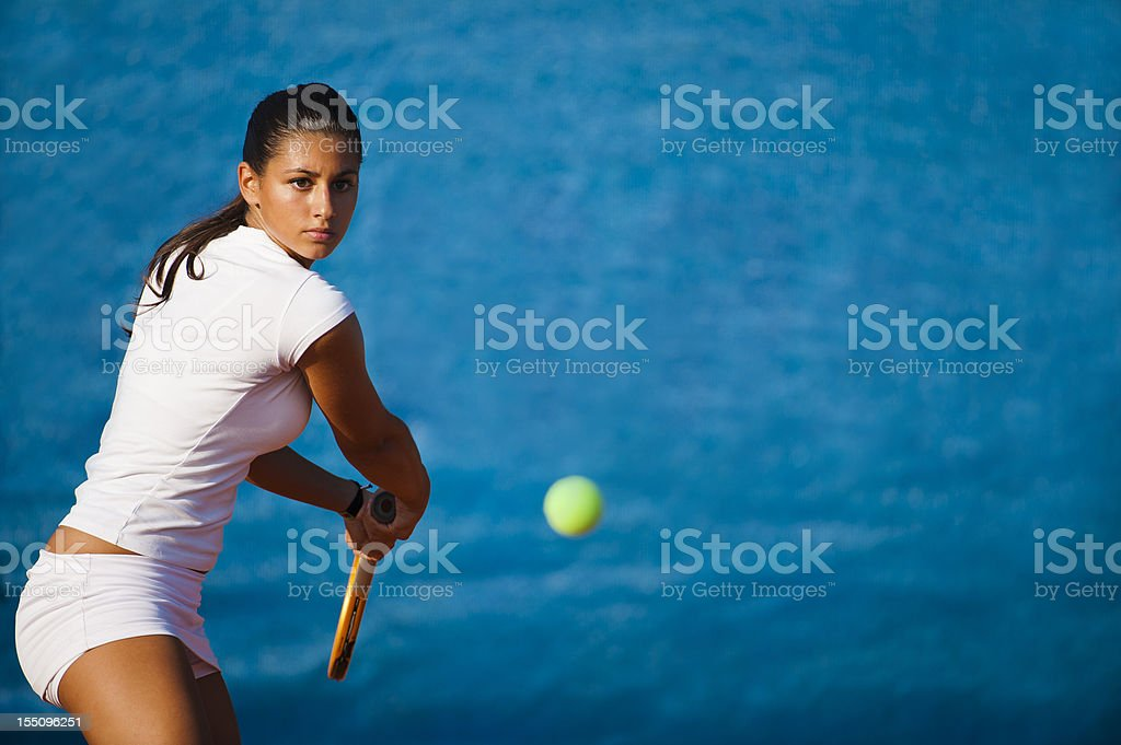 Female tennis player on the blue background stock photo