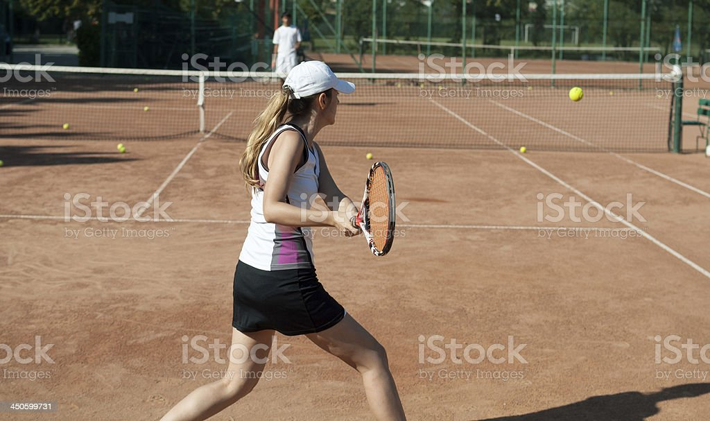 female tennis player running for ball stock photo