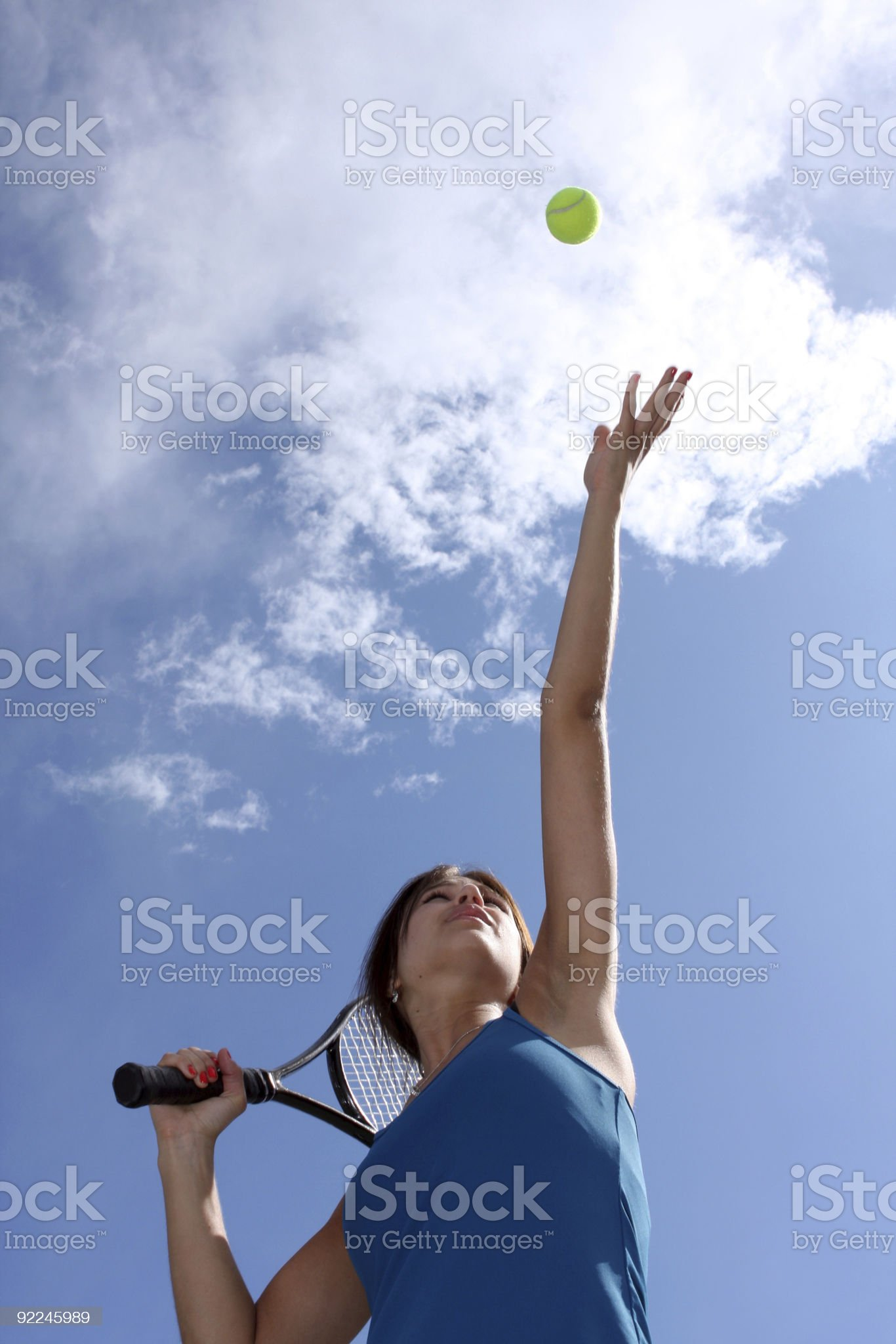 Female Tennis Player Tossing a Serve royalty-free stock photo