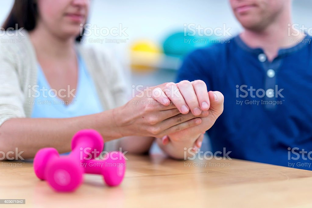 Female therapist adjusting adult males wrist for therapy stock photo