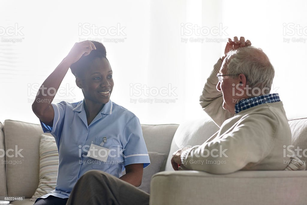 Female therapist carrying out EFT treatment with senior client stock photo