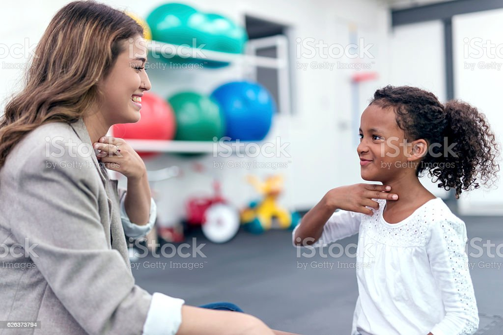 Female therapist helping African American girl in speech therapy exercise stock photo