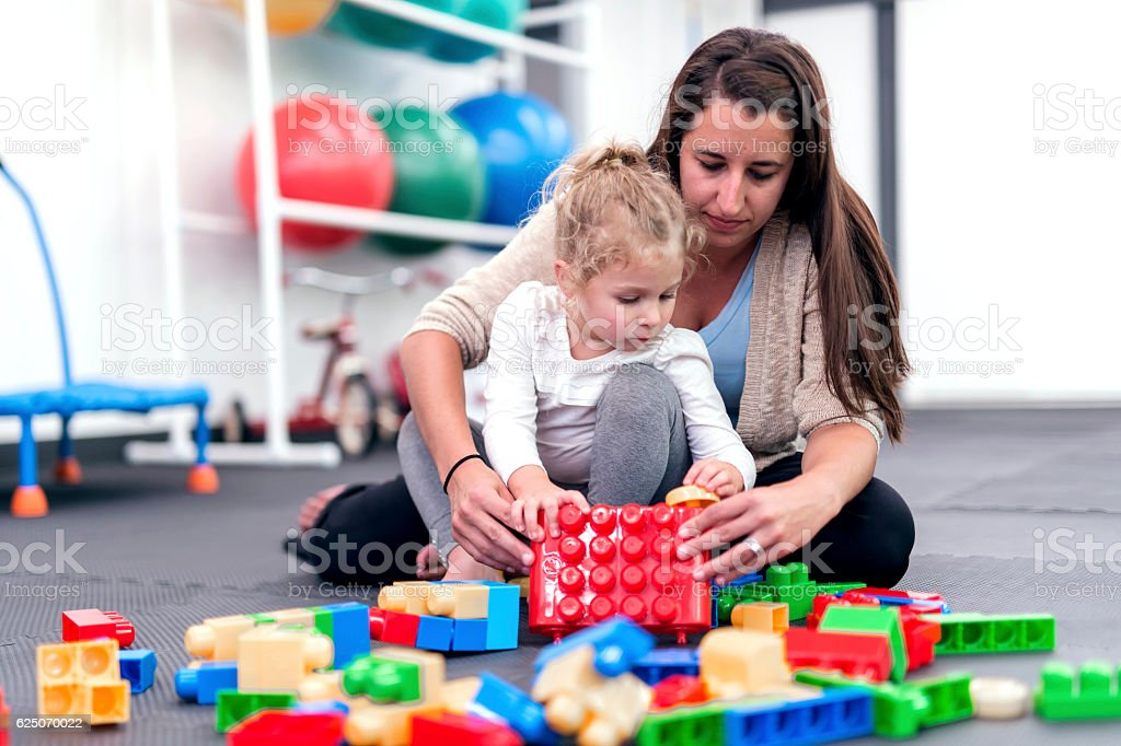 Female therapist helps young girl with a building exercise stock photo