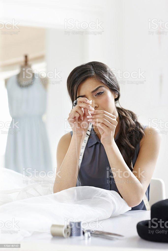 Female threading the needle at fashion studio royalty-free stock photo