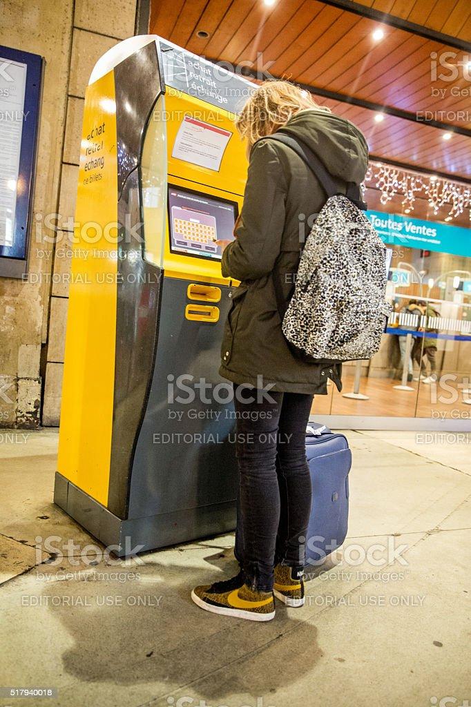Female ticket machine user at Paris Railway Station stock photo