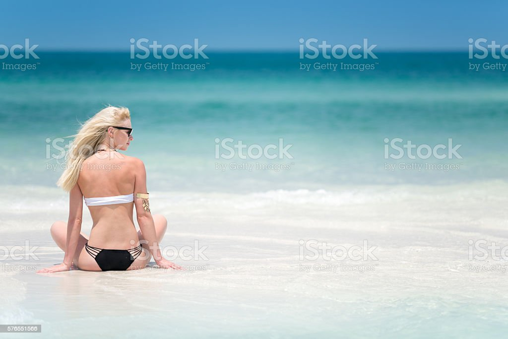 Female Tourist enjoying her Vacation, Perfect Day at the Beach, stock photo