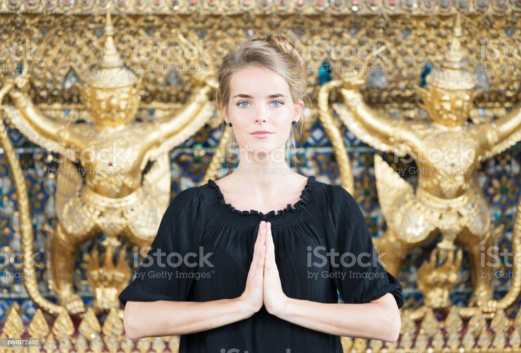 Female Tourist meditating at the Grand Palace in Bangkok, Thailand stock photo
