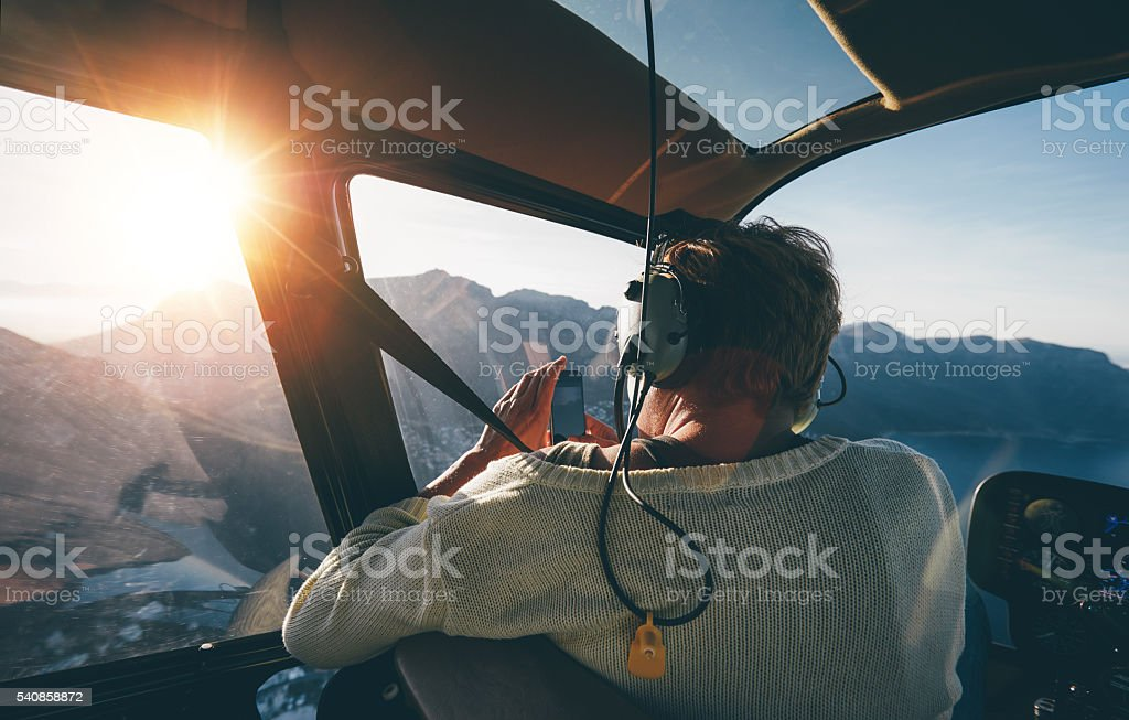 Female tourist on helicopter tour taking pictures stock photo