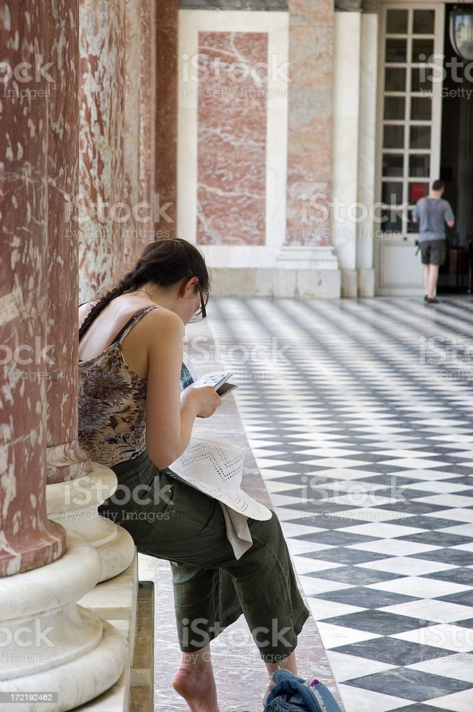 Female Tourist Resting on Column Reading a Museum Guidebook royalty-free stock photo