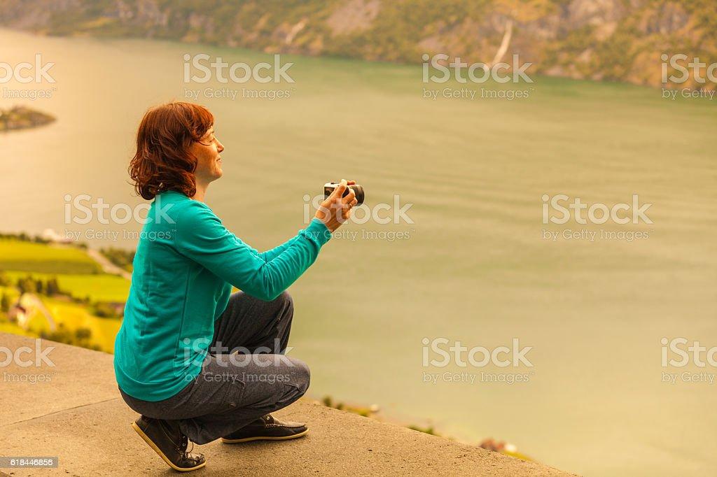 Female tourist taking photo at norwegian fjord stock photo