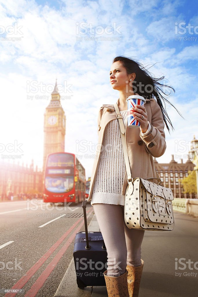 Female tourist walking with luggage at Big Ben in London stock photo