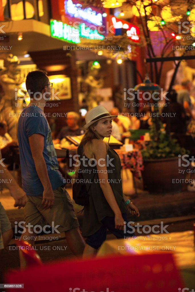 Female tourist with straw hat in Khao San Road at night stock photo