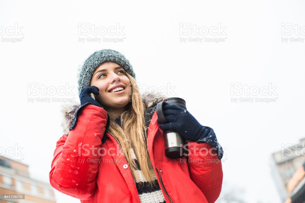 Female tourist with travel mug talking on cellphone stock photo