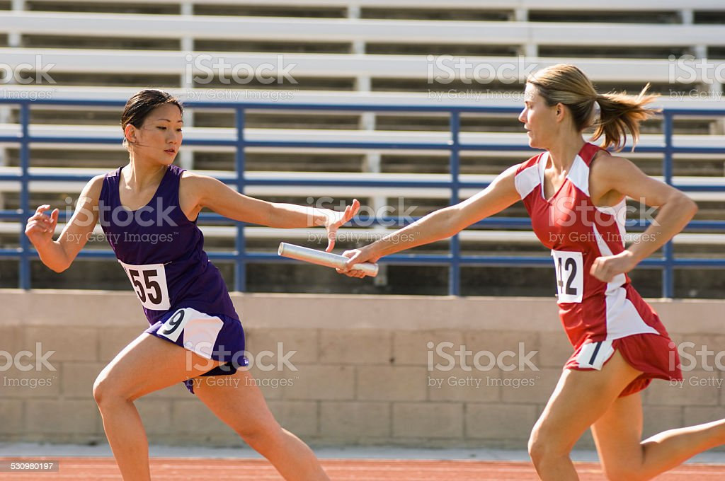 Female track athlete passing relay baton stock photo