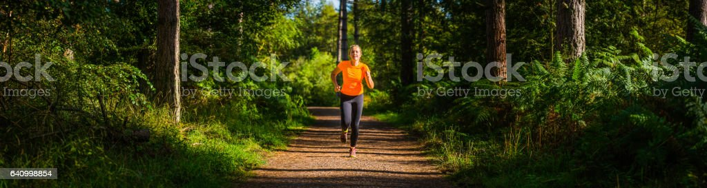 Female trail runner running along forest track through idyllic woodland stock photo