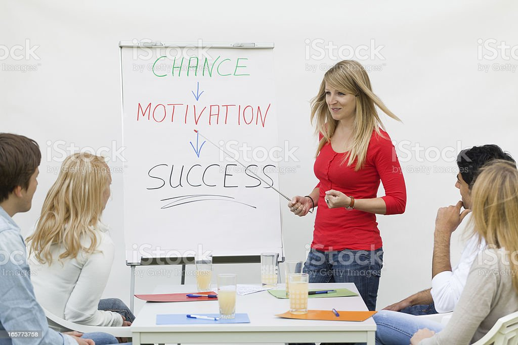 Female trainee at flipchart talking to students royalty-free stock photo
