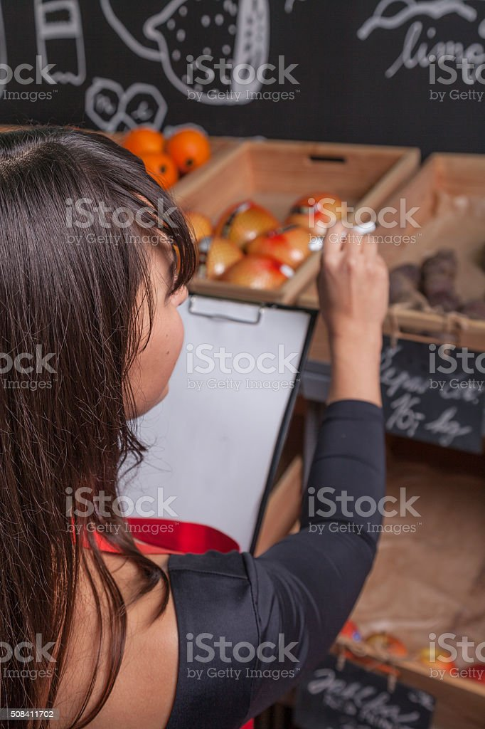 female trainee counts fruits while the inventory stock photo