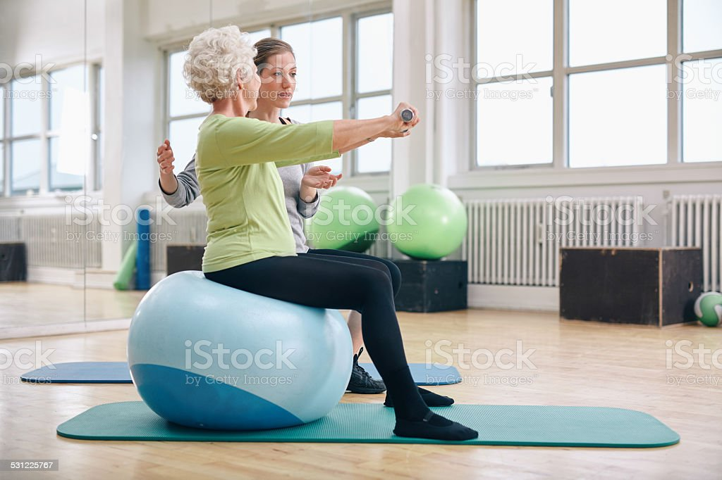Female trainer assisting senior woman lifting weights stock photo