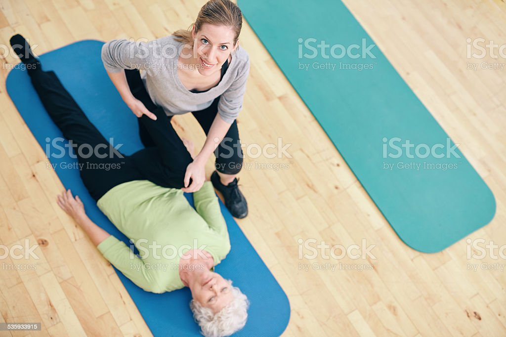 Female trainer helping senior woman do leg stretches at rehab stock photo
