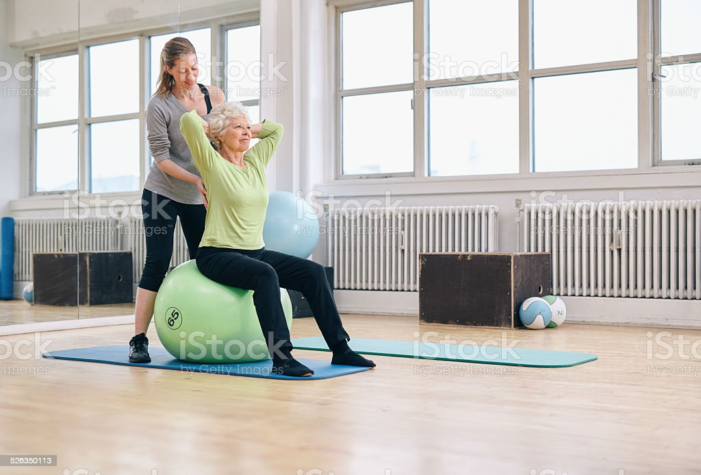 Female trainer helping senior woman exercising in gym stock photo