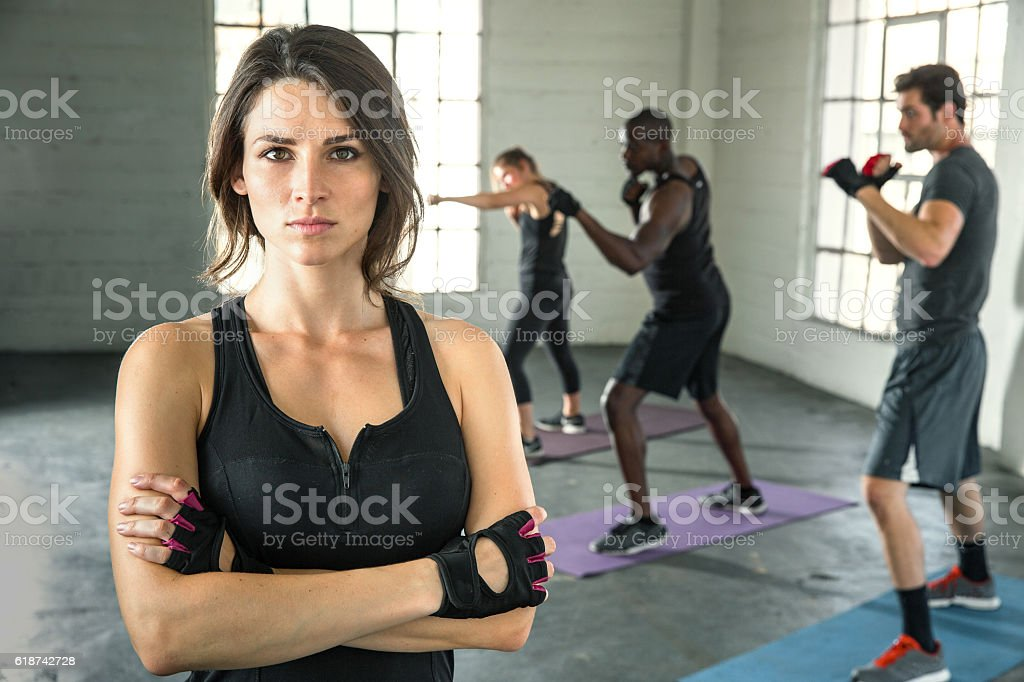 Female trainer instructor gym arms crossed fighter leader mma class stock photo