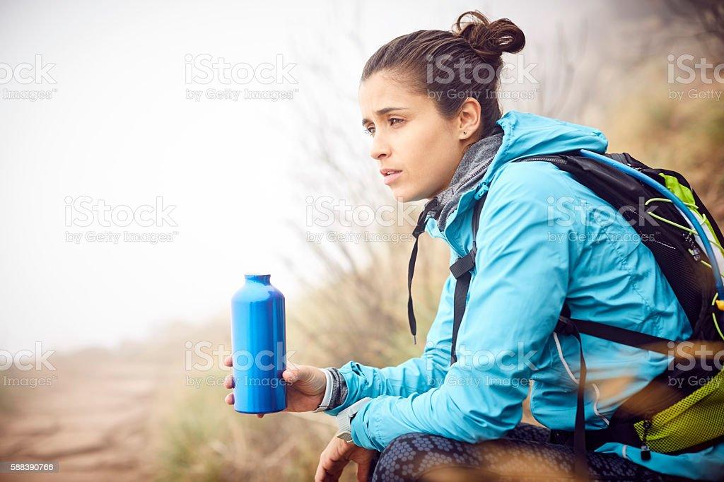 Female traveler holding water bottle during foggy weather stock photo