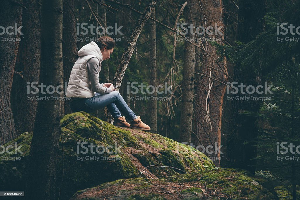 Female traveler uses a smartphone in a forest stock photo