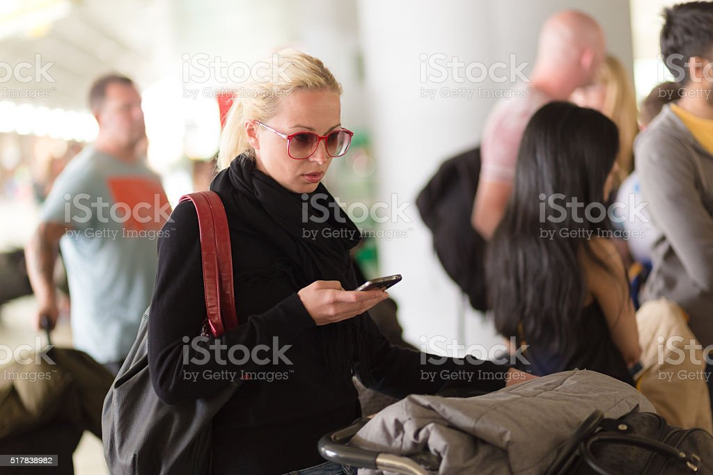 Female traveler using cell phone while waiting on airport. stock photo
