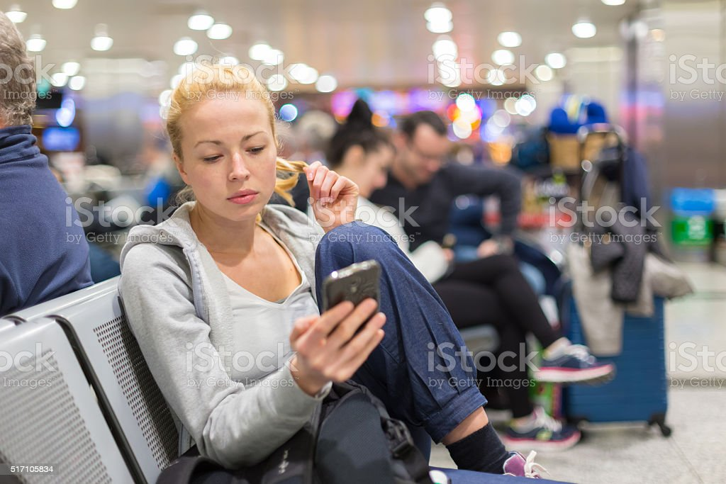 Female traveler using cell phone while waiting. stock photo