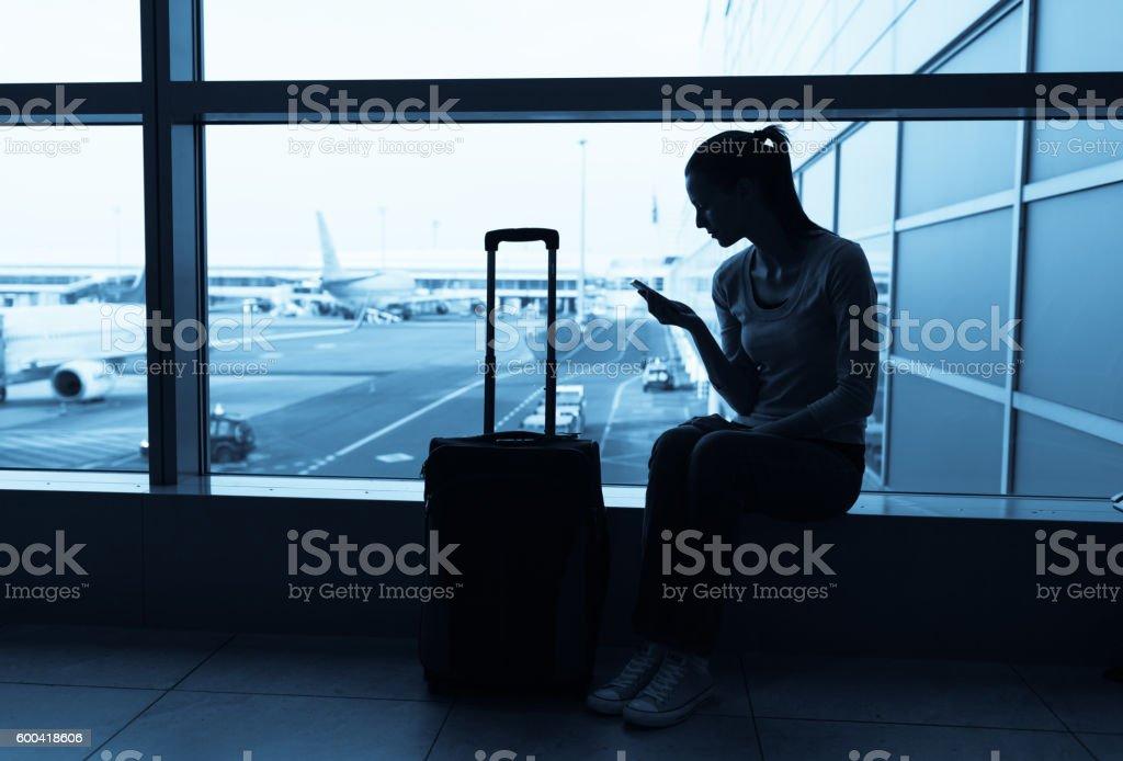Female traveler using her cellphone stock photo